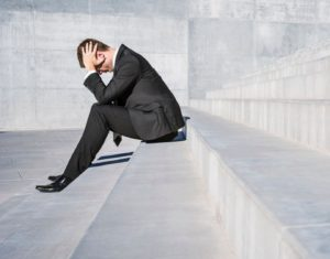 Businessman sitting on concrete steps with head in hands